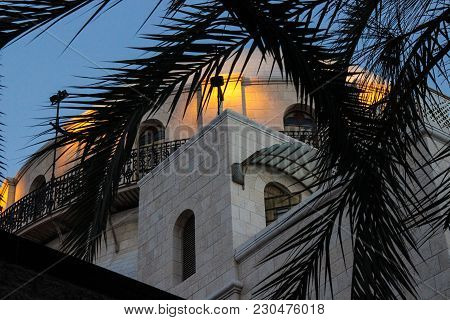 Beautiful White Building Of Interesting Design In Front Of Palm Leaves