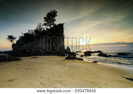 Tropical Beach Over Sunrise Background. Gigantic Beach Rock On Sandy Beach