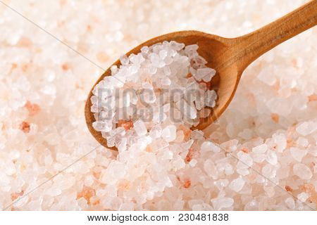 spoon of coarse grained salt on coarse grained salt background - close up