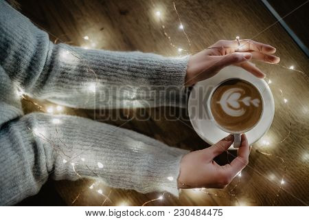 Girl Holding Coffee In Hands Over Light Bokeh Background. Nice Winter Photo Of Hands With Coffee Cup