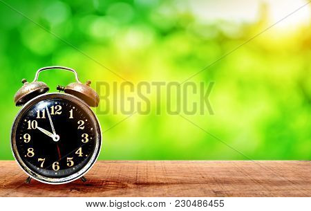 Retro Clock On Wooden With Nature Green Bokeh Background On A Light Green - Dark Green