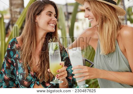 Pretty Brunette Woman Clinks Cocktail With Her Best Female Friend, Meet Together After Summer Holida