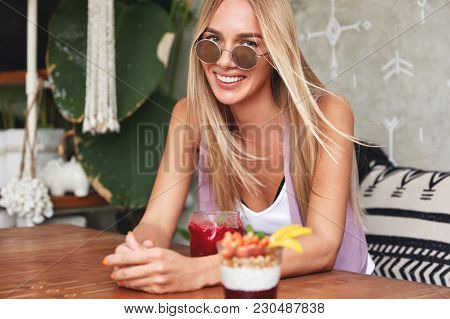 Photo Of Cheerful Relaxed Female Model Recreats At Coffee Shop, Has Positive Smile, Eats Summer Swee