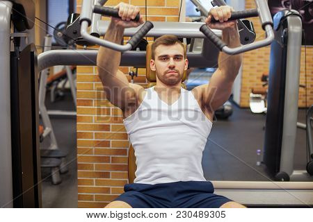 Man Exercising At Gym. Fitness Athlete Doing Chest Exercises On Vertical Bench Press Machine.