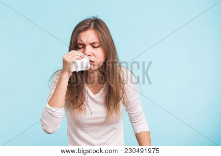 Young Woman Has A Runny Nose On Blue Background.