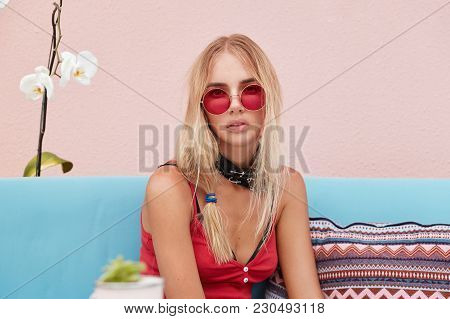 Portrait Of Serious Blonde Woman In Trendy Sunglasses, Wears Fashionable Clothing And Red Sunglasses