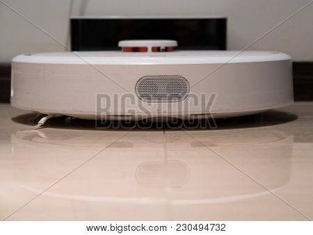 Generic White Robotic Vacuum Cleaner Front View Recharging On The Base