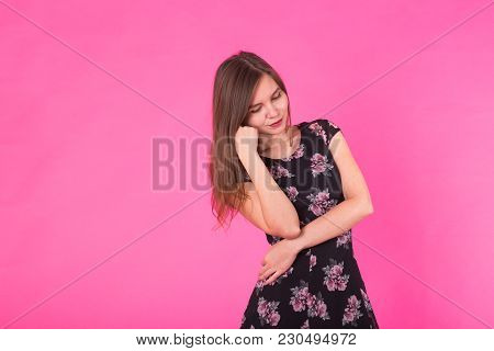 Smiling Beautiful Young Woman In Pink Mini Dress Posing, Presenting Something And Looking Away. Thre