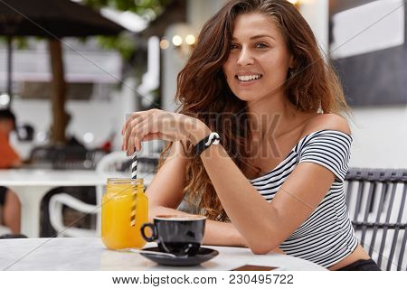 Indoor Shot Of Happy Pretty Woman Rests With Friends In Cafeteria, Has Satisfied Expression, Looks P