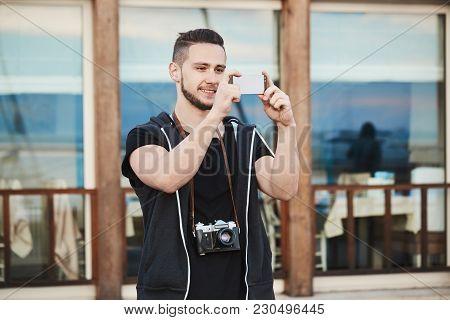 Photographers Love This Smartphone. Outdoor Portrait Of Handsome European Photographer In Trendy Clo