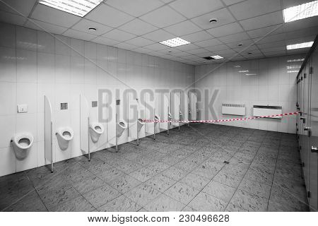 Non Working Public Toilet Or Wc With Warning Tape. Urinals In Public Restroom For Men.