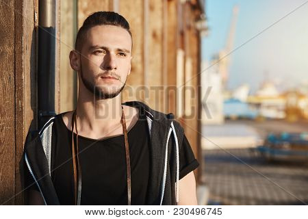 Photographer Feels Great After Hardworking Day. Dreamy Handsome Man Leaning On Wall While Looking As