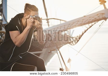 Man Is Searching For Best Shots. Focused Photographer During Work Standing Near Yacht Bending While