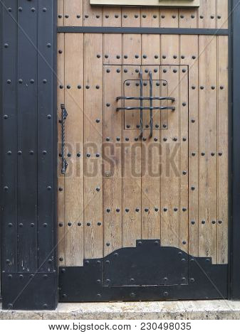 Large Wooden Door With Traditional Arabic Studs And Iron Bars In Almeria, Spain