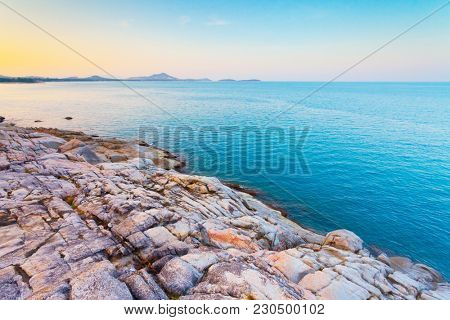 The pile of the boulders next to the calm blue ocean. The kingdom of Thailand. Ideal background in beige, blue shades for the different kinds of the marine illustrations and collages.