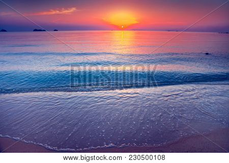 Wonderful scene the sand shore and calm water surface of the Indian Ocean next to the exotic tropical islands in the kingdom of Thailand. Amazing sunset in the red, orange and gold tints.
