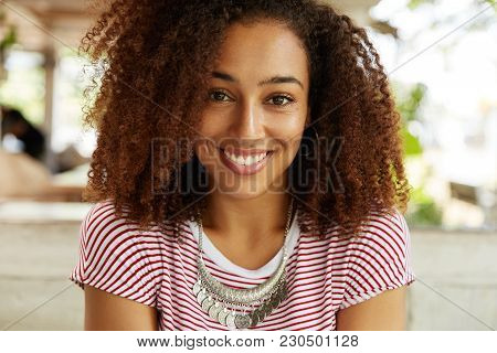 Portrait Of Happy Of Dark Skinned Female With Curly Bushy Afro Hairstyle, Smiles Broadly Into Camera