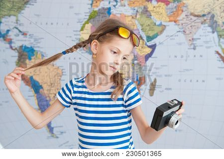 pretty little girl holding vintage camera and her pigtails on background of world map poster