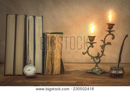 Old Book And Feather Pen With Inkpot And Rusty Key On Retro Wooden Table Background In The Light Of