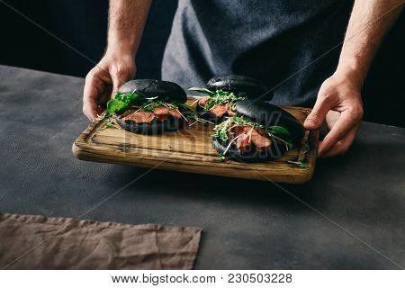 Man Holding Black Burger Beef Medium Rare Spinach Sauce
