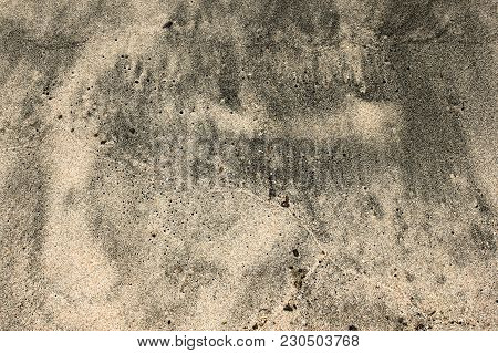 Brown And Gray Wet Sand Texture On The Beach Of Lake Baikal. Dotted Sand Floor With Lines Of Waves,