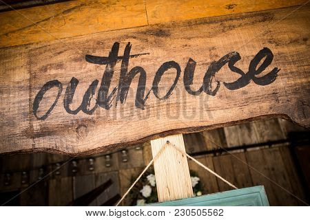 Black Handwritten Outhouse Sign On Unpainted Wooden Board In Close-up