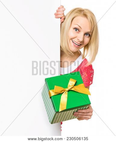 Portrait of happy smiling young woman, showing empty blank signboard with copyspace. Businesswoman holding gift box and peeping behind blank board, isolated on white background.