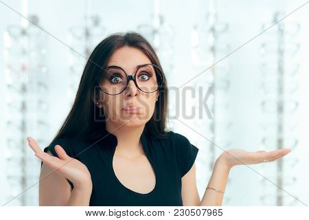 Undecided Woman Surrounded By Glasses In Eyeglasses Store