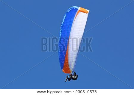 Tandem Paraglider Flying Wing In A Blue Sky