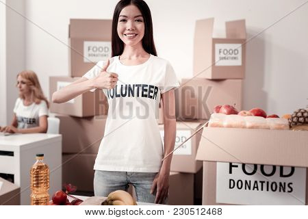 I Like It. Attractive International Girl Being Volunteer, Keeping Smile On Face And Standing On The