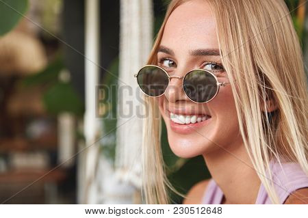 Close Up Shot Of Cheerful Blonde Young Woman Wears Round Shades, Has Broad Smile And Appealing Appea