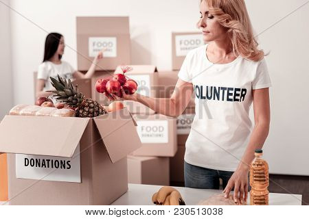 Fresh Fruits. Attentive Woman Pressing And Turning Head While Checking Parcel With Donations