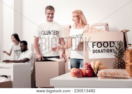 Focused Photo. Positive Delighted Female Talking To Her Colleague And Pointing At Empty Parcel While