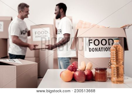 Help Me. Two Colleagues Holding Big Box With Food Donations, Looking At Each Other While Standing In