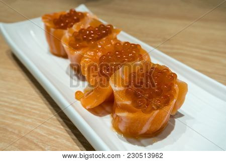 Fresh Raw Salmon Sushi Roll With Fish Egg Roe On Long White Plate Closeup Macro
