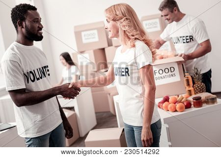 Dividing Products. Handsome African Man Keeping Smile On His Face And Standing Inn Semi Position Whi