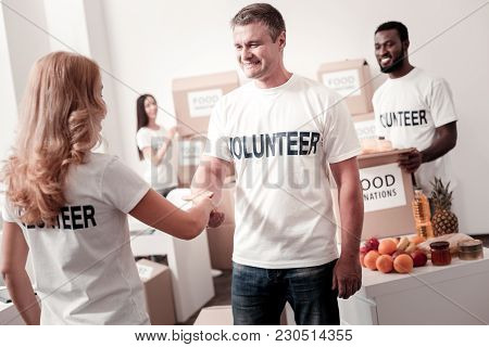 Nice To Meet You. Positive People Wearing White T-shirts And Gathering Products While Going To Send