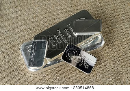 Several Silver Bars Against The Background Of The Texture Of Coarse Cloth. Feinsilber Is Fine Silver