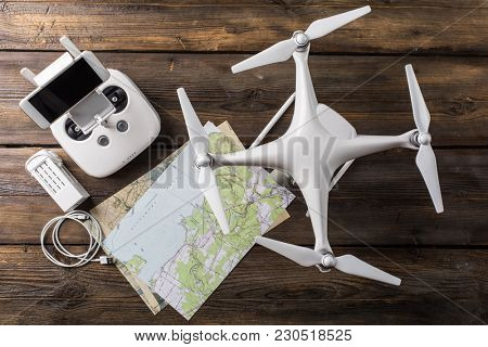 Drone equipment. Remote control, drone, screw, map on gray background. Top view