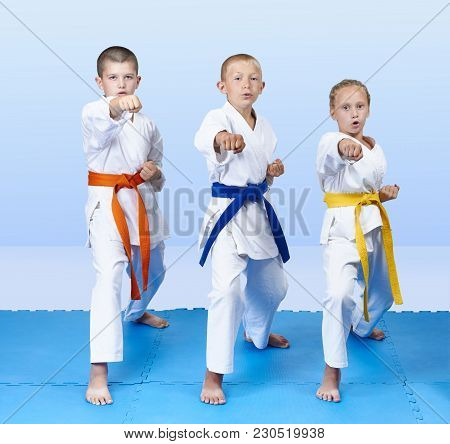 Three Sportsmen With Belts Of Different Colors Hit Punch Arm