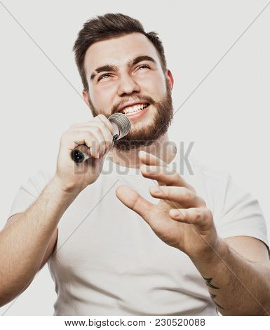 The entertainer. Young  talking man holding microphone, Isolated on white background.