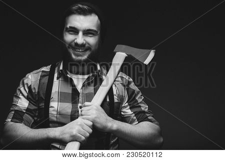 Bearded man with axe posing over black background in studio