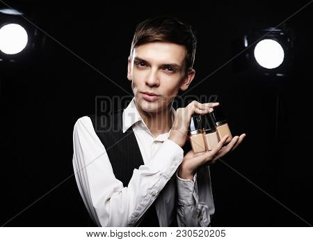Young male make up artist posing  with foundation for make-up o