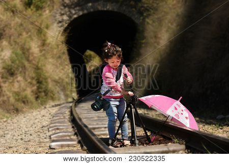 Little Girl Photographer With Tripod And Dslr Camera Strapped On Her Neck