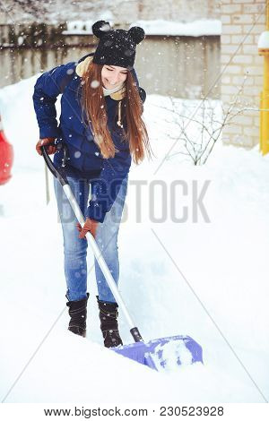 Winter Portrait Of A Young Woman Cleaning Snow. Beauty Joyous Model Girl Laughing And Having Fun Wit
