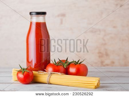 Glass Bottle Of Tomato Paste With Raw Spaghetti And Fresh Organic Tomatoes On Wooden Background