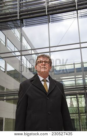 Confident And Determined Businessman In Suit Standing In Front Of Modern Glass Building Looking Up