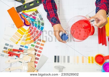 Asian Professional Decorator Drawing On A House Project With Work Tools.