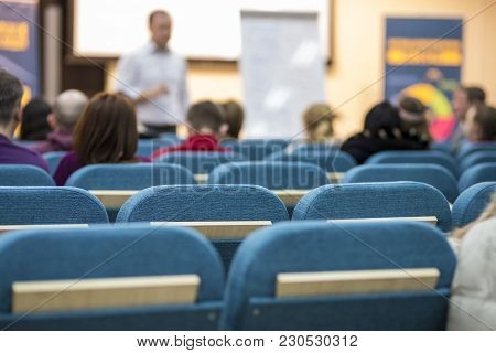 Meetings Concepts. People Listening To A Male Presenter Holding A Conference In Front Of A Group Of