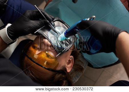Dentist Performs Dental Treatment To A Patient In Orange Dental Glasses With A Rubberdam